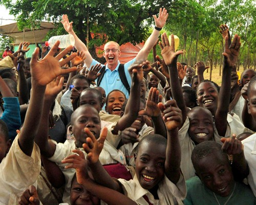 U.S. Air Force Senior Airman Daniel McKittrick, a public affairs broadcaster, assigned to Combined Task Force - Horn of Africa (CJTF-HOA), celebrates with children before a water project dedication ceremony in Magu, Tanzania, Jan. 21, 2008. The Magu water project provides clean drinking water to thousands of villagers in the Magu region of Tanzania and is a example of how CJTF-HOA develops and nurtures partnerships to promote regional cooperation and create an environment for development (U.S. Air Force photo by Staff Sgt. Joseph L. Swafford Jr./Released)